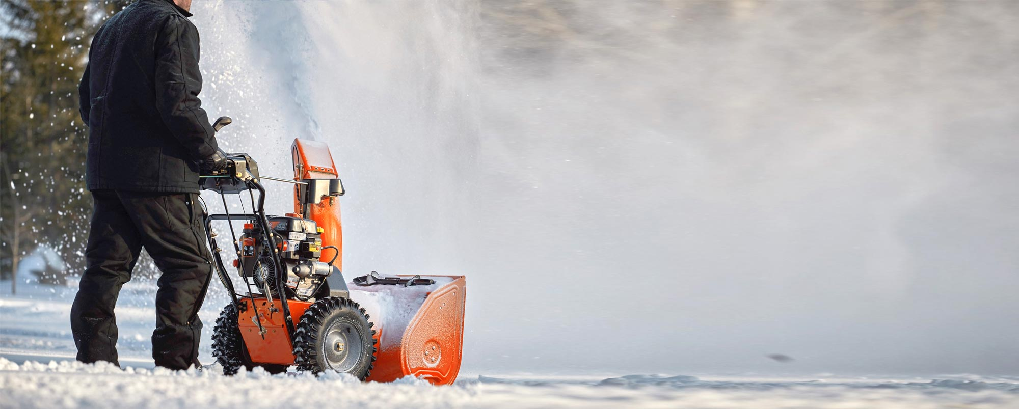 Man using an orange Ariens Snowblower to move snow in the winter